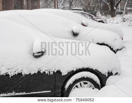 Cityscape - parked cars covered with snow