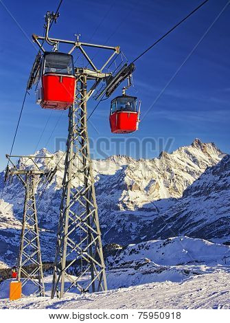 Red Cable Cars On The Cable Railway On Winter Sport Resort In Swiss Alps