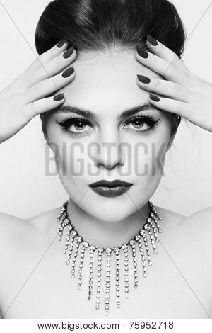 Black and white portrait of young beautiful woman with stylish make-up and manicure