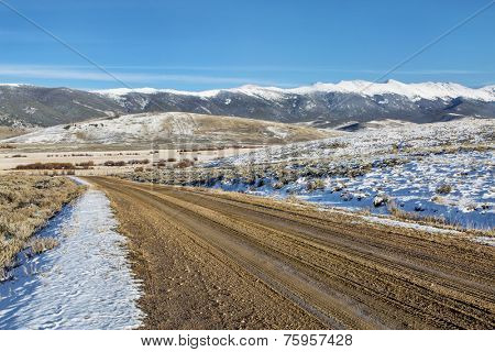 dirt backcountry road with  snowy Medicine Bow Mountains in background, North Park near Walden, Colorado, late fall scenery