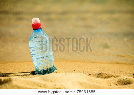 Beverage Bottle Of Water Drink On A Sandy Beach.