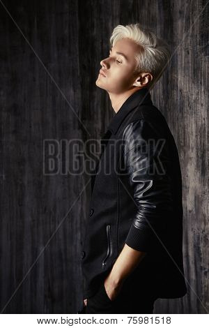 Portrait of a beautiful male model with blond hair wearing black jacket. Urban style. Fashion.