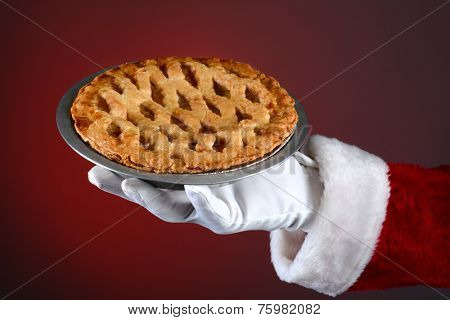 Santa Claus hand holding a fresh baked apple pie over a light to dark red background. Horizontal format showing only Santa's hand and arm.