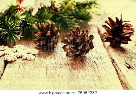 Christmas decorations with fir tree branch cones on a light wood background