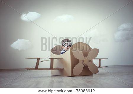 Little boy with a cardboard airplane