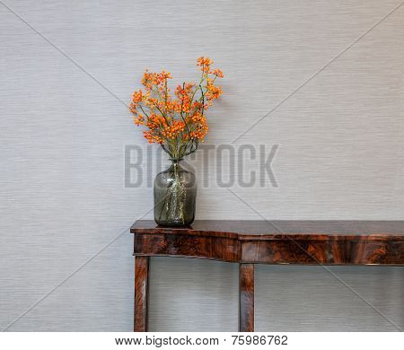 Sideboard In Front Of A Grey Wall With Flower Vase