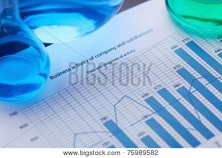 Test-tubes with blue and green liquids on document with financial data