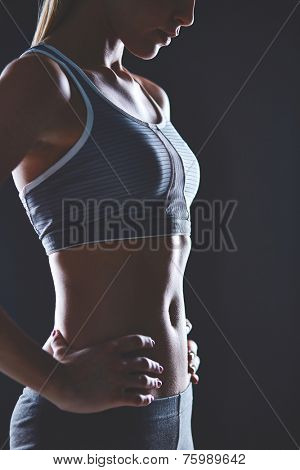 Body of slim female in activewear keeping her hands on waist