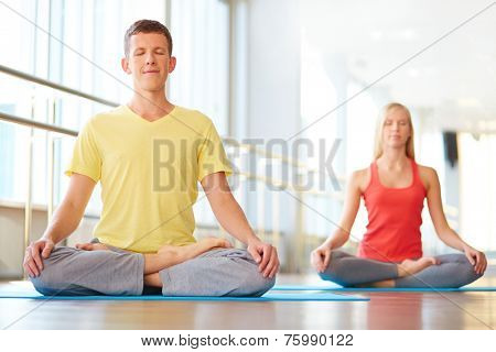 Relaxed guy meditating in pose of lotus with girl on background