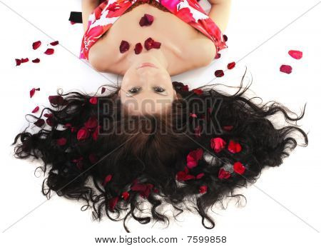Young Girl Lies In Petals Of Roses