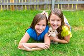 stock photo of twin baby girls  - twin sister kid girls and puppy dog happy playing with pet lying in backyard lawn - JPG