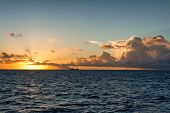 image of cumulus-clouds  - Colorful marine sunset over a tropical ocean with the fiery orange sun dipping down towards the horizon with low lying cumulus cloud formations in a twilight sky - JPG