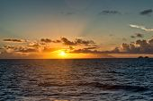 stock photo of orbs  - Glowing orange sunset over the ocean as the orb of the sun dips below the horizon at twilight - JPG