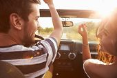 picture of road trip  - Young Couple Driving Along Country Road In Open Top Car - JPG