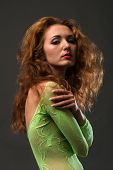 stock photo of fishnet stockings  - Slender young redheaded woman in a green fishnet body stocking - JPG