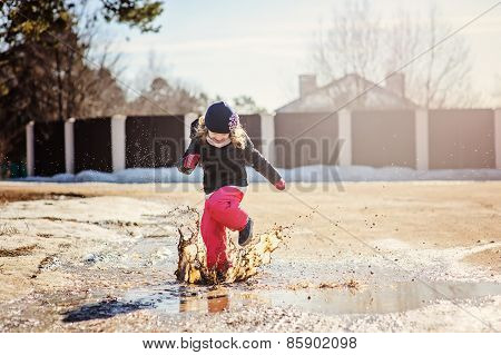 child girl jumping in spring puddle with splashes