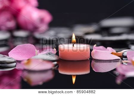 rose with petals with candle and therapy stones