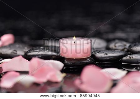 Beautiful pink rose petals with candle and therapy stones