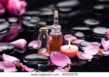 rose with petals and candle ,oil with therapy stones