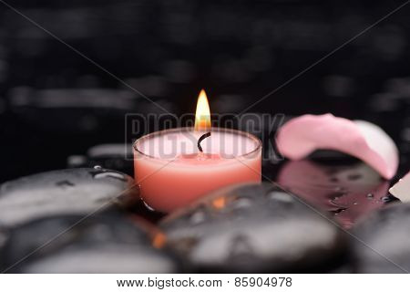 rose petals with pink candle and therapy stones