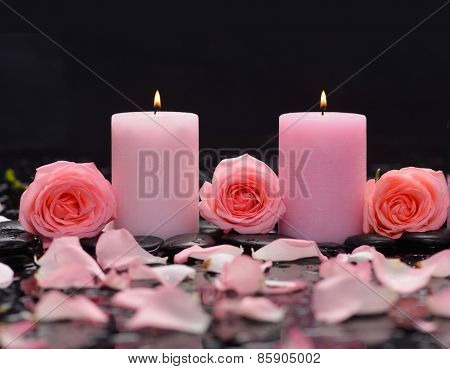 Three pink rose, petals with candle and therapy stones