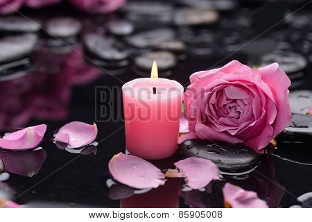 Beautiful pink rose with candle and therapy stones ,