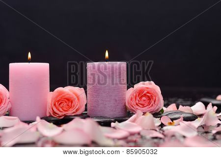 Lying down three rose with petals and two candle with therapy stones