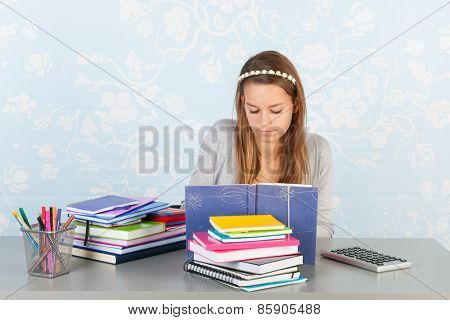 Teen girl sitting at desk with homework for school