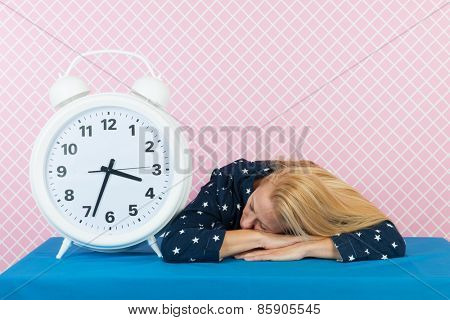 Woman of mature age laying next to big alarm clock