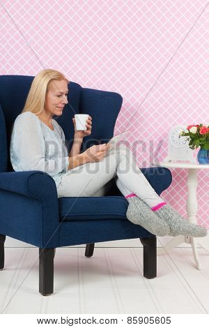 woman relaxing with digital tablet in living room