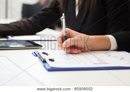 Closeup of a woman taking notes during a meeting