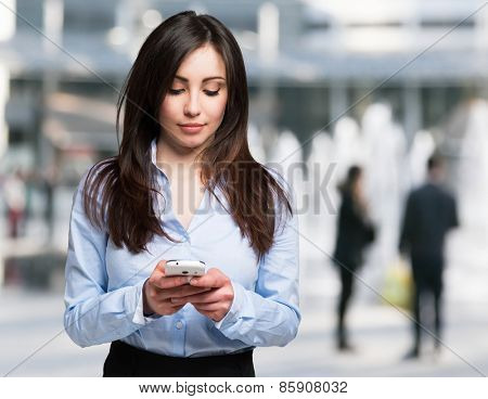 Modern woman using a mobile phone in a modern urban district