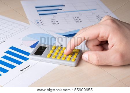 Business Concept - Graphs, Charts And Male Hand With Calculator