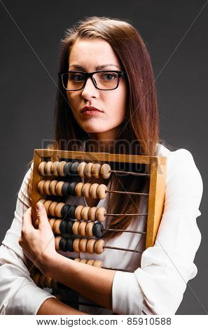 Portrait of business woman with abacus on gray background
