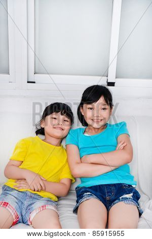 Portrait of little girl sister sitting sofa