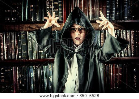A boy in black cape with hood stands in the library by the bookshelves with many old books. Fairy tales. Halloween. Vintage style.