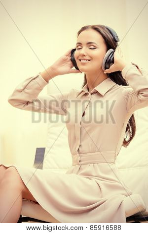 Happy young woman resting at home listening to music in headphones.