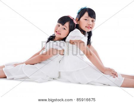 Two girls sitting back to back in studio