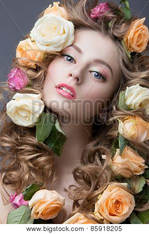 Portrait of a beautiful girl with a gentle pink make-up and lots of flowers in her hair. Beauty face