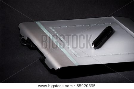 Design tablet on black background, low key photo