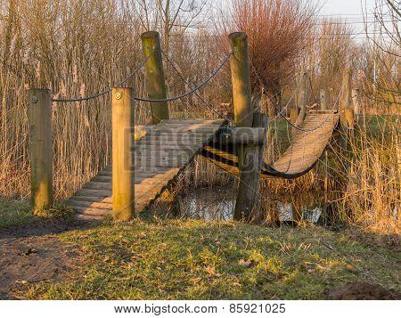 Wooden Footbridge Over Stream By Sunset