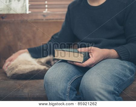Young Man Sitting On A A Sofa With A Cat And A Big Book
