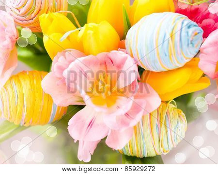 Easter Background. Holiday flowers bunch and Easter eggs closeup. Colorful tulips flowers bouquet decorated with colourful eggs. Easter art design. Springtime