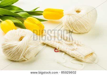 Roll Of White Soft Knitting Yarn, Knitting Mittens And Yellow Tulips