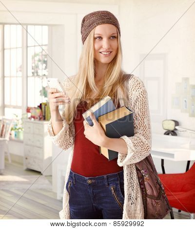 Happy blonde college student leaving for school, holding books and mobile.