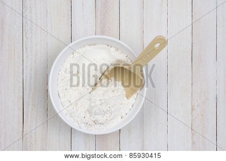 Overhead image of a bowl of flour on a white wood rustic kitchen table. A plastic scoop is stuck in the flour.
