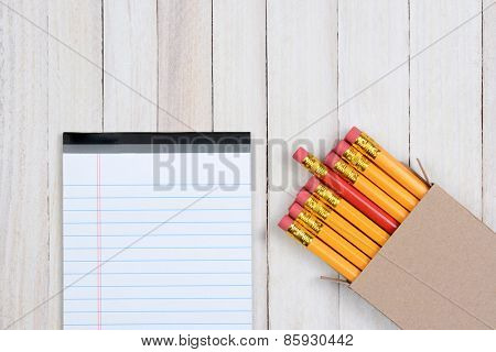 A box of yellow pencils with one red pencil partially pulled out. The plain brown box is in the lower right corner of the frame at an angle, and a blank note pad is next to the box.