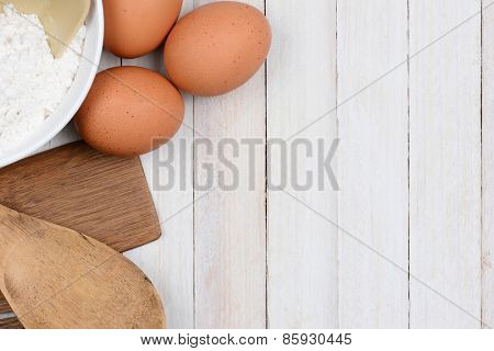 High angle image of a bowl of flour brown eggs and wood kitchen utensils on a rustic white wood table. Items are set ot one side leaving copy space.