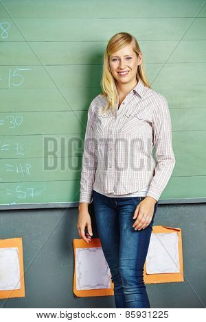 Smiling woman standing in front of chalkboard in elementary school