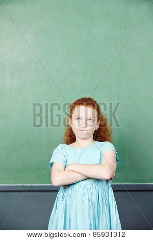Pensive girl in front of a chalkboard in elementary school